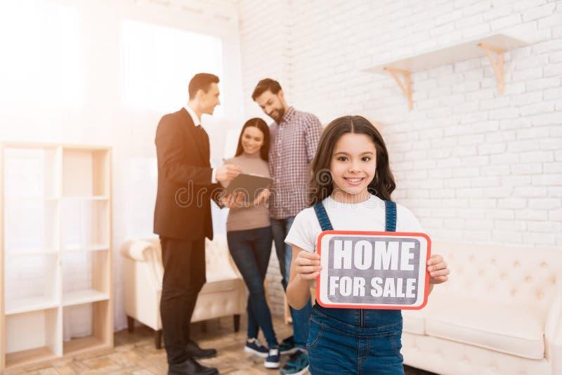 Маленькая девочка держит знак с надписью расквартируйте сбывание Риэлтор показывает квартиру к парам стоковые фото