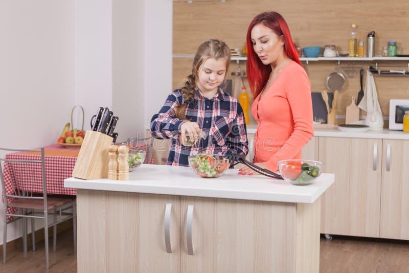 Маленькая девочка добавляя масло к ее вкусному зеленому салату стоковая фотография rf
