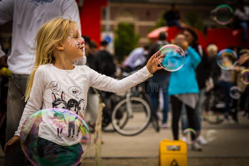 Маленькая девочка достигая вне для того чтобы касаться пузырю мыла стоковое фото rf