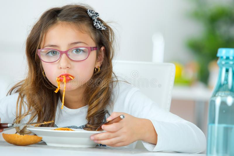 Маленькая девочка есть спагетти дома стоковые фотографии rf