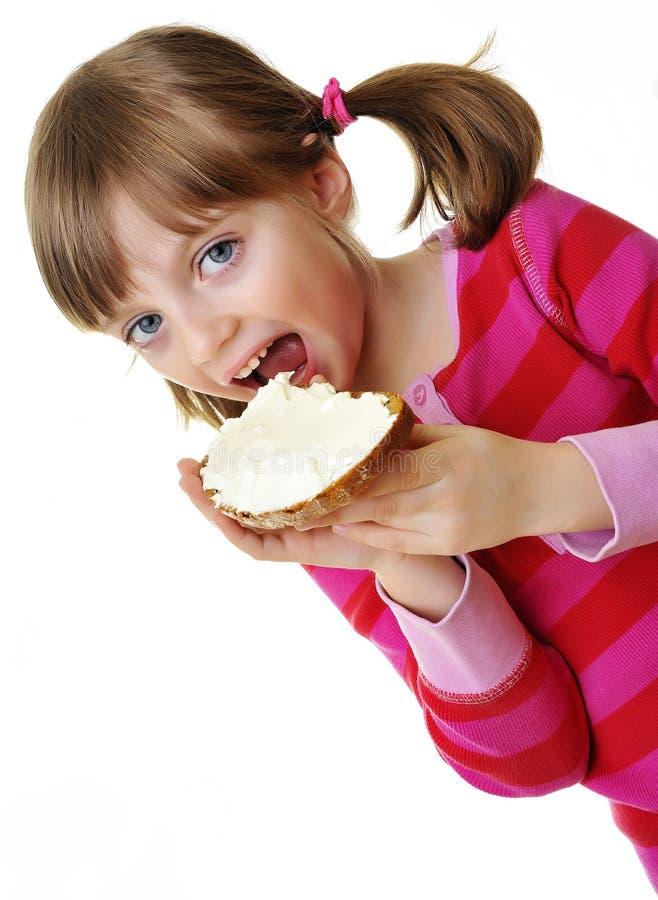 Маленькая девочка есть хлеб с сыром стоковая фотография