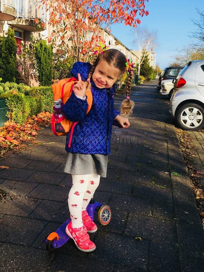 Маленькая девочка ехать самокат на пригородной улице стоковое изображение rf