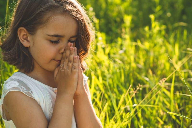 Маленькая девочка закрыла ее глаза, моля в поле во время красивого захода солнца Руки сложенные в концепции молитве для веры стоковое фото rf