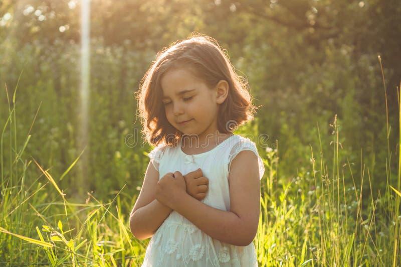 Маленькая девочка закрыла ее глаза, моля в поле во время красивого захода солнца Руки сложенные в концепции молитве для веры стоковое фото