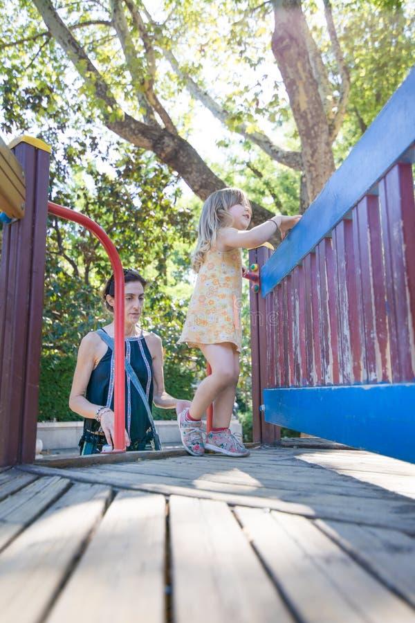 Маленькая девочка играя в спортивной площадке с матерью стоковое изображение rf