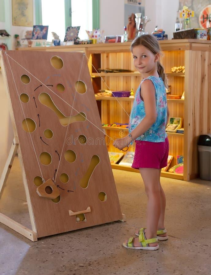 Маленькая девочка играя деревянную мышь игры лабиринта в сыре Винтажная игра лабиринта доски с веревочками стоковая фотография rf