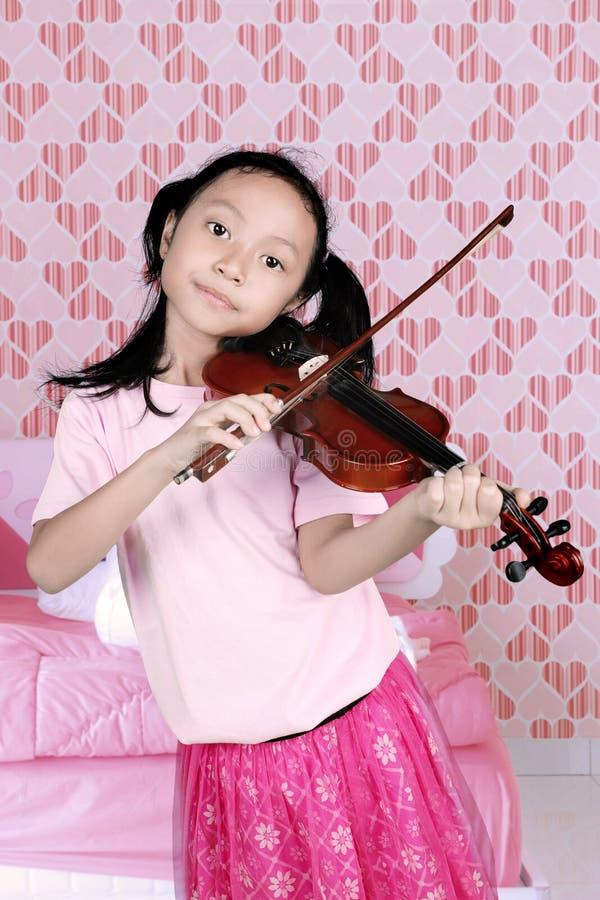 Маленькая девочка играя музыку с скрипкой стоковые фотографии rf