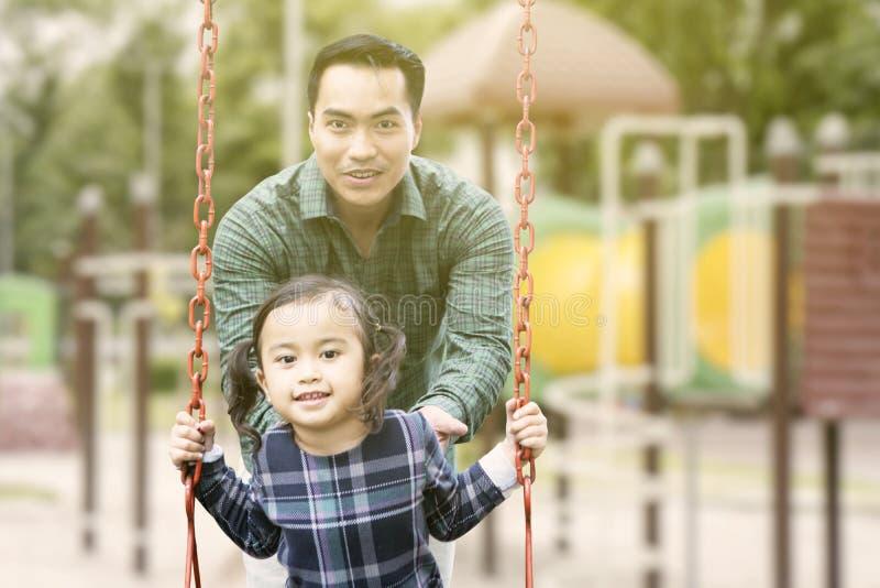 Маленькая девочка играя на качании с ее отцом стоковое изображение rf