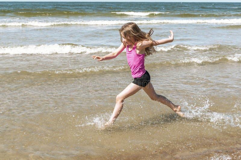 Маленькая девочка играя на пляже стоковая фотография rf
