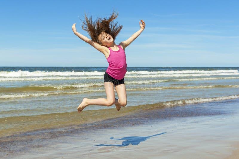 Маленькая девочка играя на пляже стоковые изображения rf