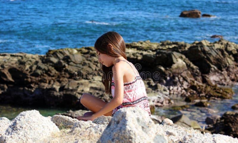 Маленькая девочка играя на фронте океана в море скалы курорта Los Cabos мексиканськом стоковое фото rf