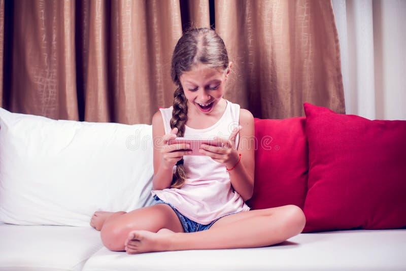 Маленькая девочка играя с мобильным телефоном дома на софе стоковые изображения rf
