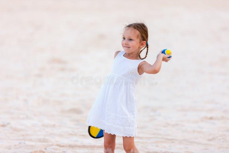 Маленькая девочка играя теннис пляжа стоковая фотография rf