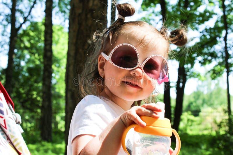 Маленькая девочка идет сидеть в pram в солнечных очках стоковые изображения