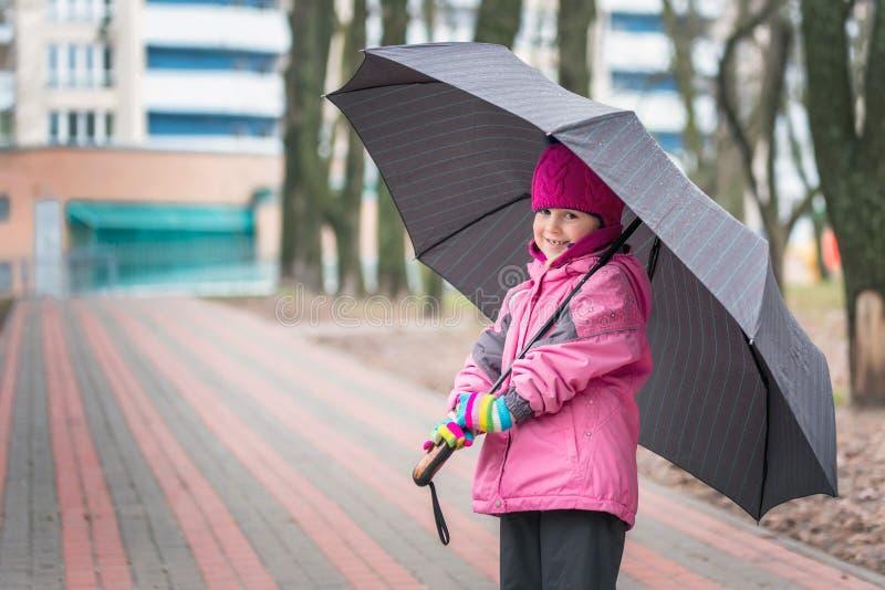 Маленькая девочка идя под зонтик в парке города стоковое изображение rf