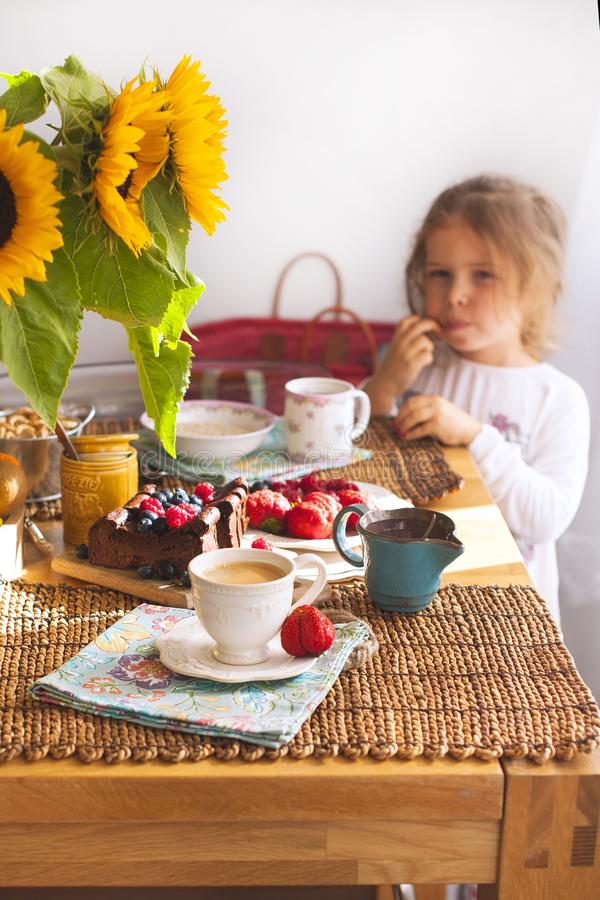 Маленькая девочка имеет завтрак дома На таблице букет цветков солнцецветов и сладостного пирога с плодоовощ, стоковое изображение