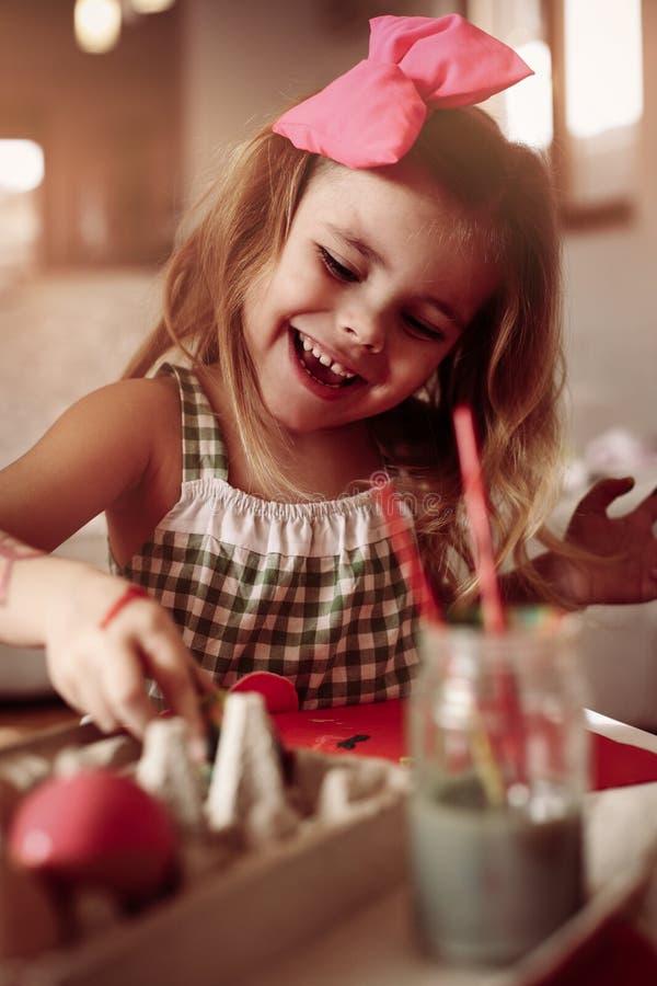 Маленькая девочка имея потеху, крася пасхальные яйца стоковые фотографии rf