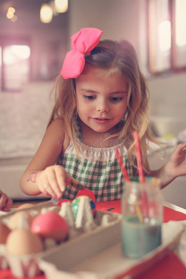 Маленькая девочка имея потеху, крася пасхальные яйца стоковые фото