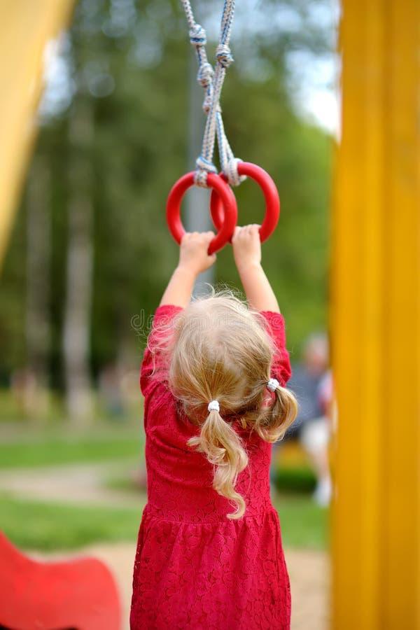 Маленькая девочка имея потеху на на открытом воздухе спортивной площадке Отдых спорта лета активный для детей Детский сад или шко стоковое фото rf