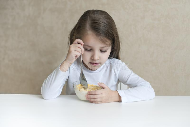 Маленькая девочка имея muesli завтрака с молоком стоковая фотография rf