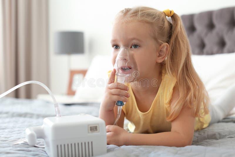Маленькая девочка используя машину астмы в спальне стоковые изображения