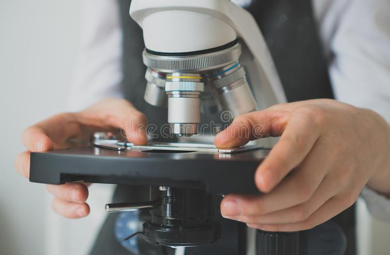 Маленькая девочка используя микроскоп стоковая фотография