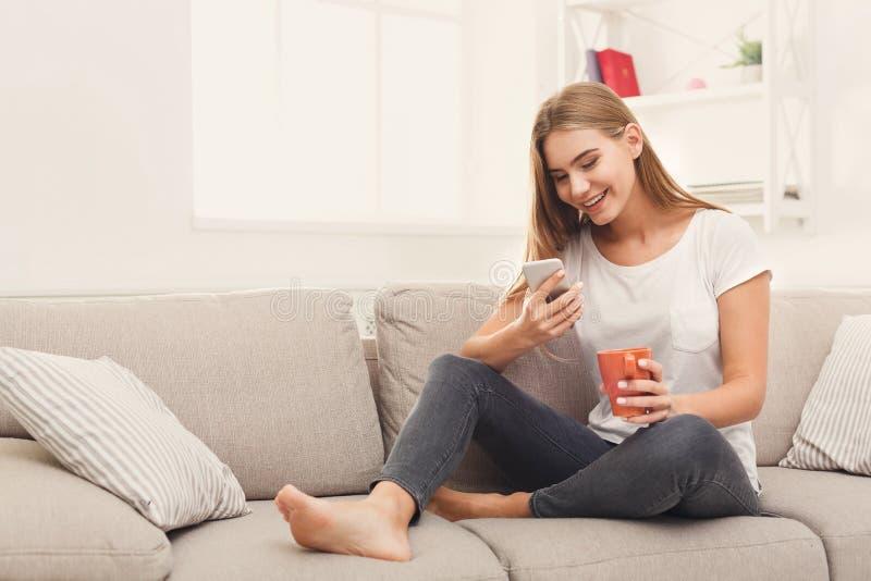 Маленькая девочка используя мобильный телефон на софе стоковое фото rf