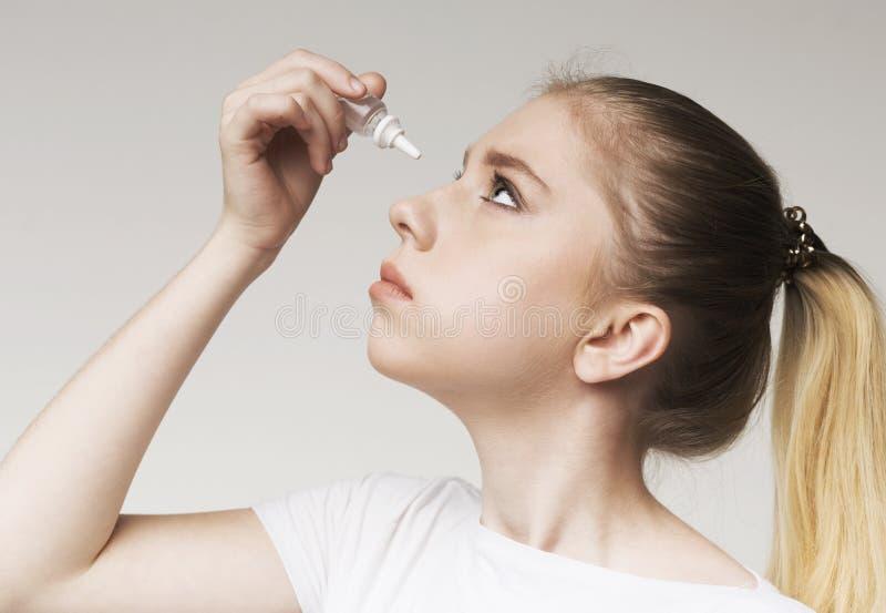 Маленькая девочка используя падение глаза контакта заболеванием стоковая фотография rf