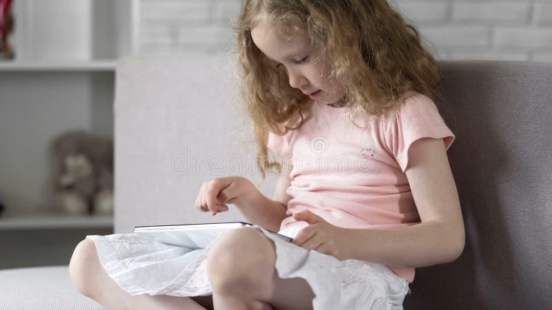 Маленькая девочка используя планшет для игры игр, современного поколения, наркомании устройства стоковое фото