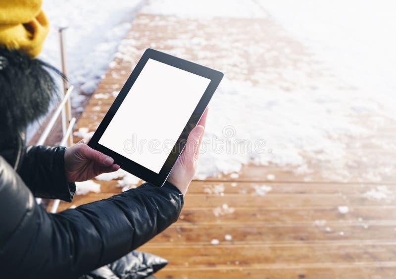 Маленькая девочка используя планшет с чистым пустым экраном на предпосылке снежных лесов и замороженных озер, прогулки в горах стоковая фотография
