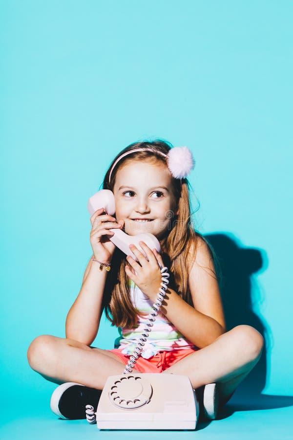 Маленькая девочка используя розовый сетноой-аналогов телефон стоковое изображение