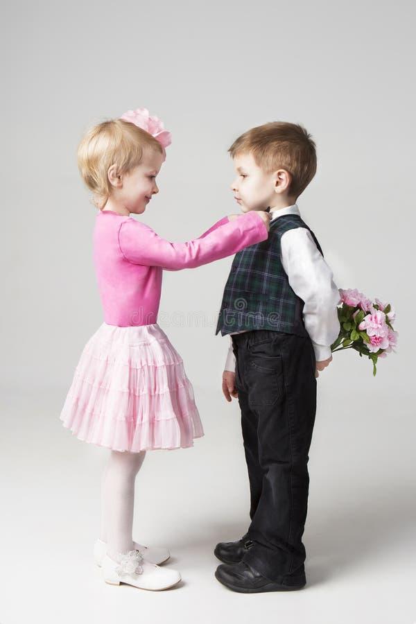 Маленькая девочка исправляет связь мальчика. стоковые изображения rf