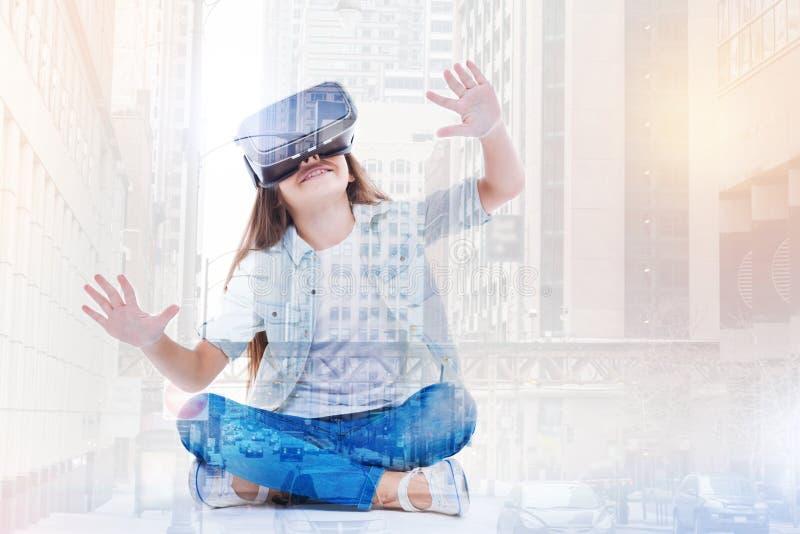 Маленькая девочка испытывая ее новый шлемофон VR пока сидящ на корточках положив ногу на ногу стоковая фотография rf