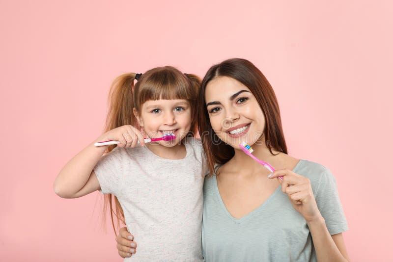 Маленькая девочка и ее зубы матери чистя щеткой совместно стоковое изображение