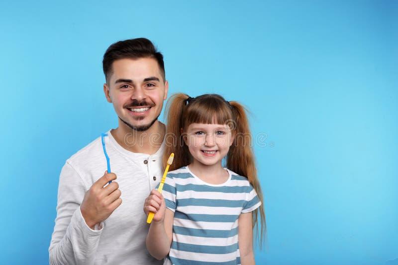 Маленькая девочка и ее отец с зубными щетками на предпосылке цвета, космосе для текста стоковое фото rf