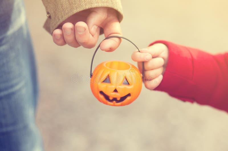 Маленькая девочка и ее отец, хеллоуин, фокус родителя и ребенка или обрабатывать совместно Ребенк малыша с Джек-o-фонариком стоковое изображение rf