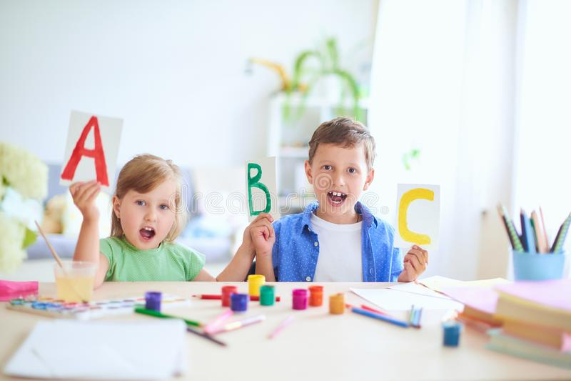 Маленькая девочка и мальчик выучить дома счастливые дети на таблице с усмехаться школьных принадлежностей смешной и учить алфавит стоковая фотография rf