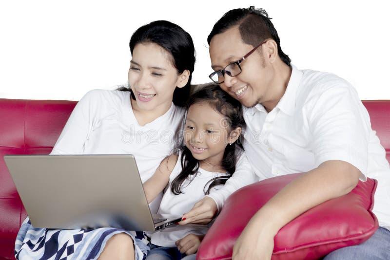 Маленькая девочка и родители с компьтер-книжкой стоковые фотографии rf