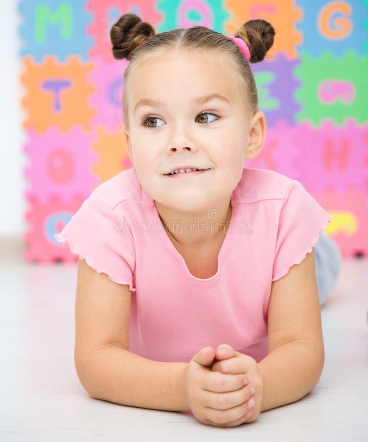 Маленькая девочка кладет на пол стоковая фотография rf