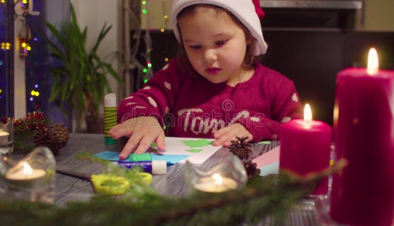 Маленькая девочка клеит карту Нового Года стоковые изображения rf