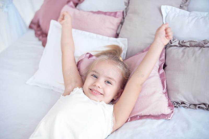 Маленькая девочка конца-вверх просыпая вверх с протягивать оружия пока бодрствующий лежать на белом постельном белье стоковое фото