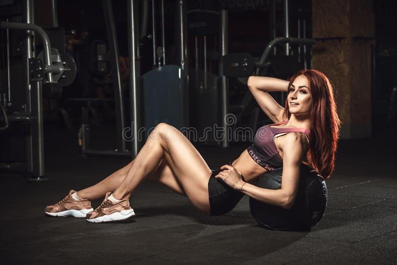 Маленькая девочка красивого фитнеса sporty лежит на шарике изгибая подбрюшные мышцы стоковая фотография rf