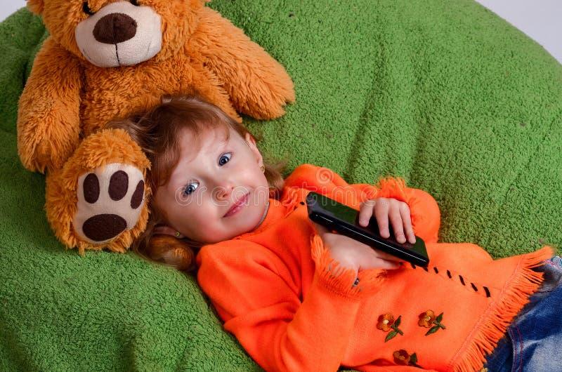 Маленькая девочка лежа на большой зеленой подушке стоковое фото rf