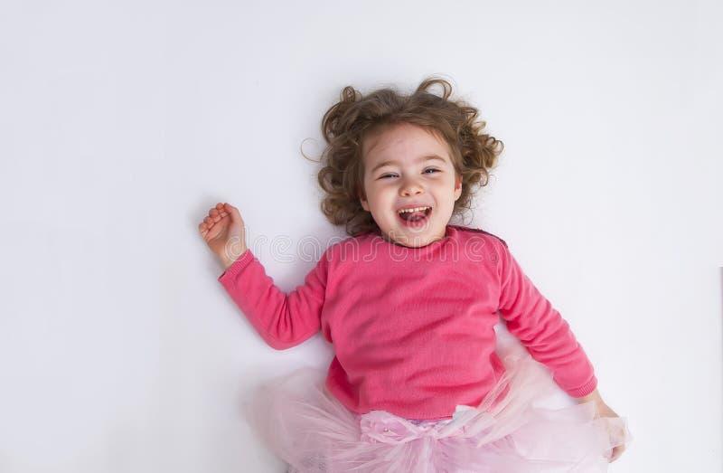 Маленькая девочка лежит на белых поле и улыбке стоковое фото
