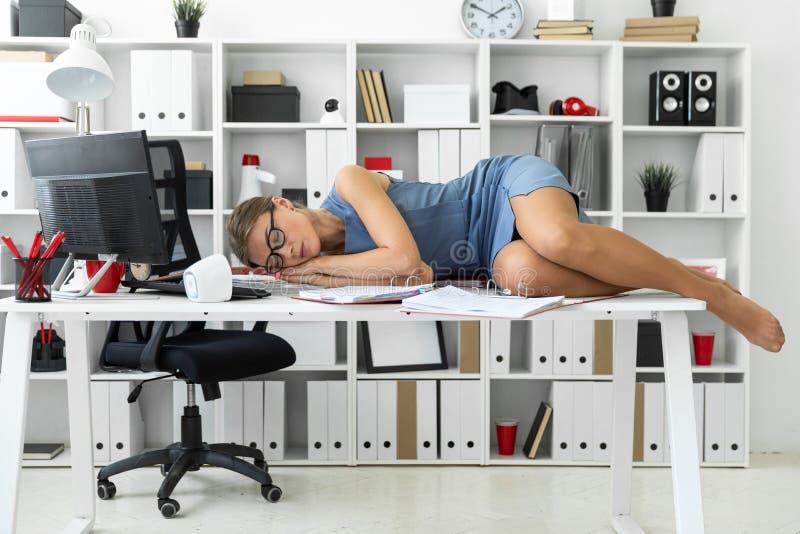 Маленькая девочка лежит с закрытыми глазами на документах на столе в офисе стоковая фотография