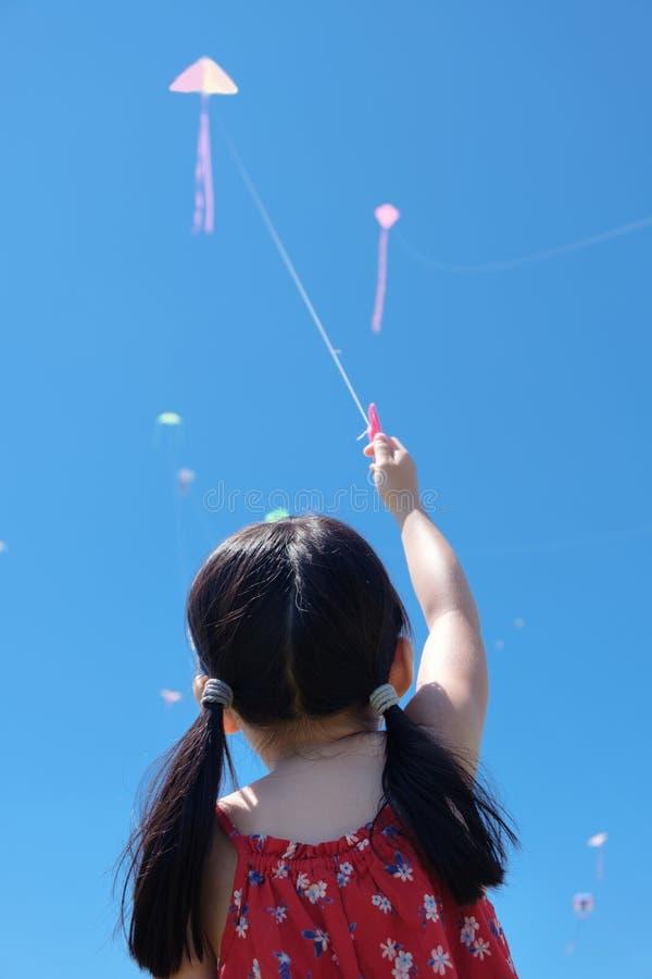 Маленькая девочка летая змей в солнечном летнем дне стоковое изображение