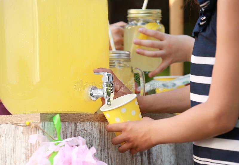 Маленькая девочка лить естественный лимонад в чашку ( стоковые фото