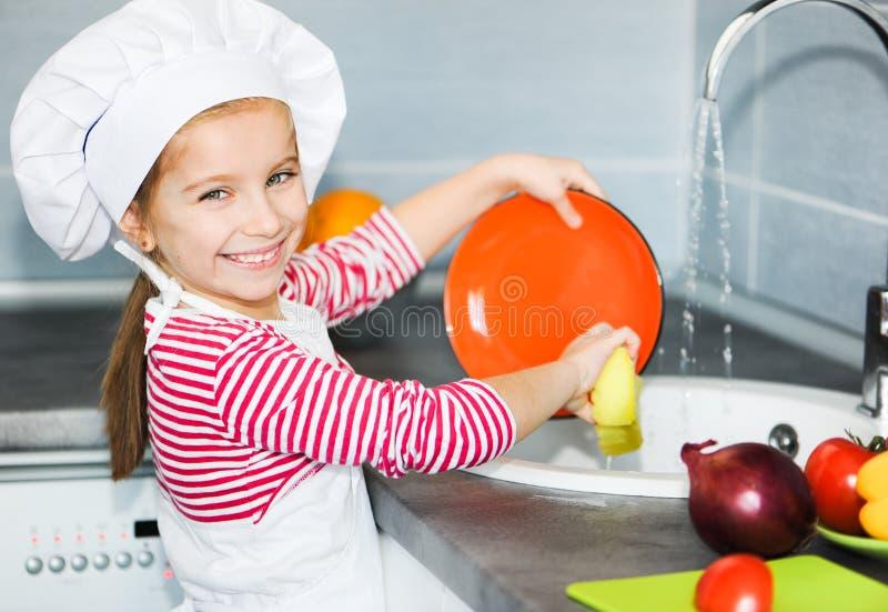 Маленькая девочка моя тарелки стоковые изображения