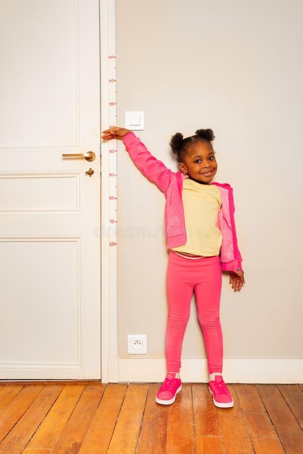 Маленькая девочка над масштабом на высоте измерения стены стоковые фотографии rf