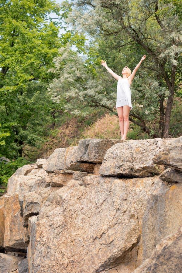 Маленькая девочка наслаждается славной погодой на крае скалы, с ей стоковые изображения